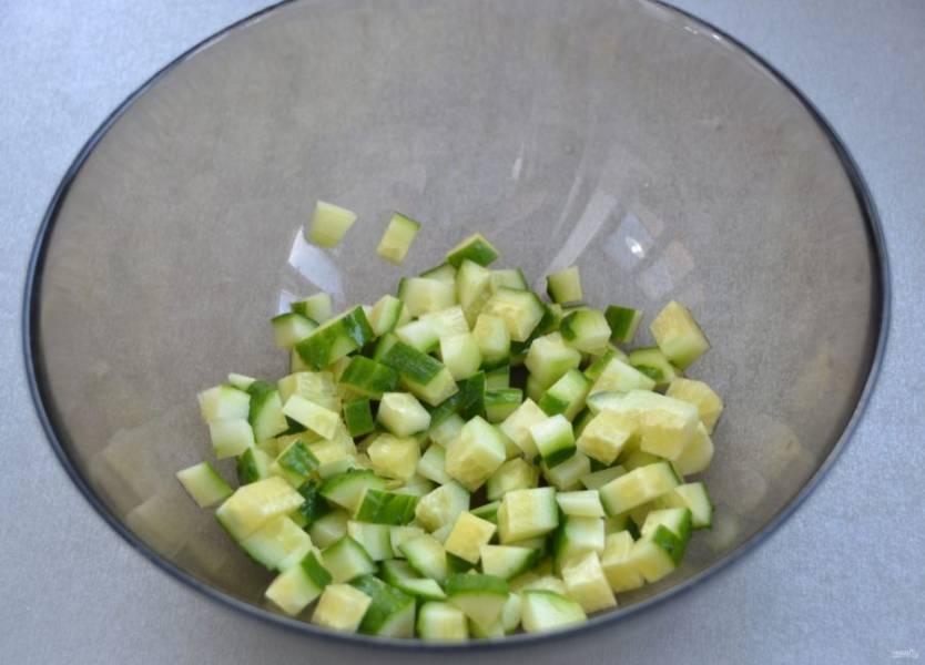 Мелким кубиком нарежьте огурец, выложите в салатник.