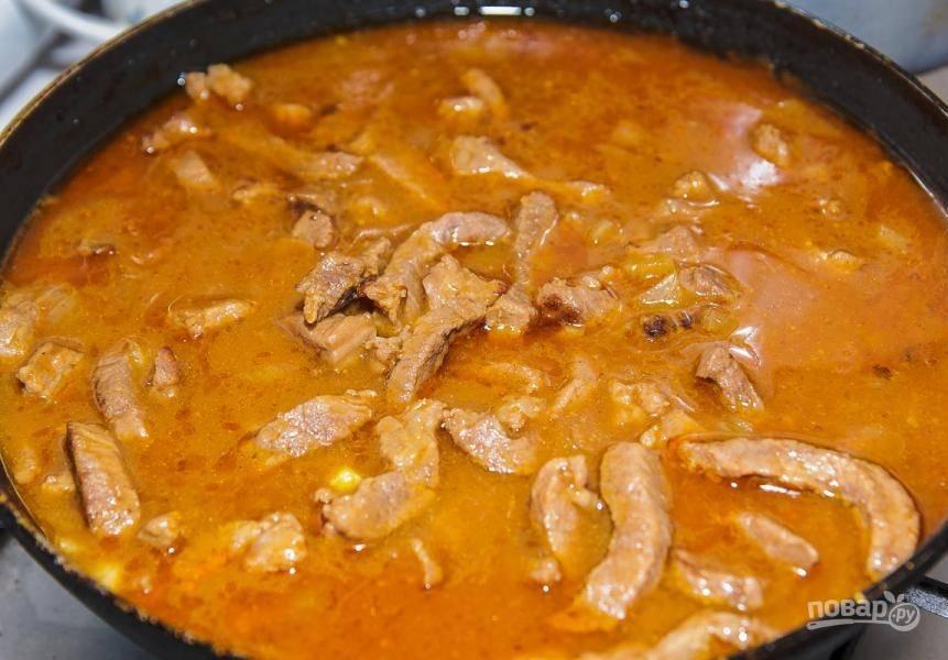Далее влейте воду. Доведите блюдо до кипения, а потом закройте сковороду крышкой. Тушите всё в течение 1 часа.