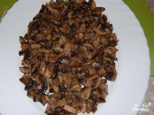 Приступаем к сборке салата, он у нас будет выложен слоями. Первый слой - обжаренные с луком грибы. Для салата можно использовать любые грибы, не только шампиньоны.