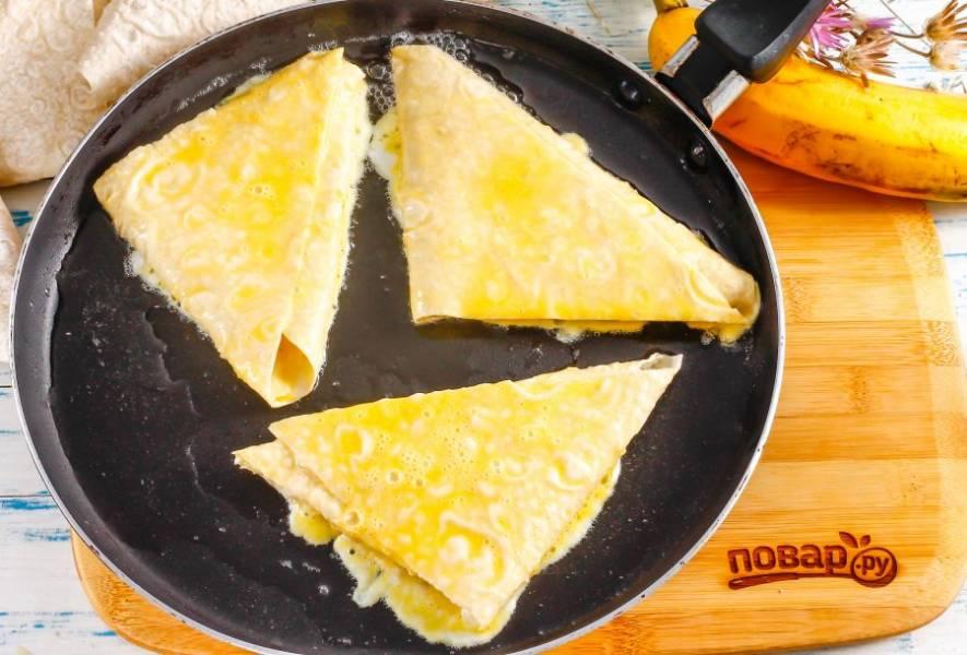 Раскалите в сковороде растительное масло и убавьте нагрев до умеренного. Обмакните заготовки во взбитую яичную массу, затем сразу же выложите в сковороду и обжарьте около 1-2 минут с одной стороны.