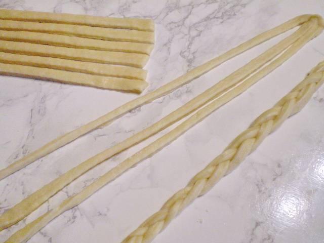 9. Перейдите на удобную рабочую поверхность, оставленную часть теста тонко раскатайте и порежьте на полосочки. Из них сплетите косички. И сделайте цветочек.