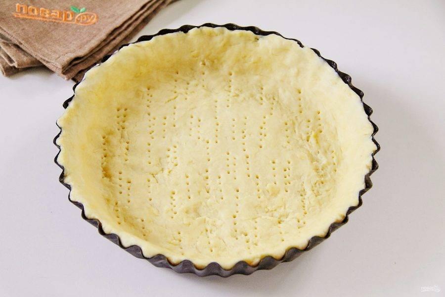 Распределяем его по смазанной маслом форме, формируя высокие бортики руками. Накалываем тесто вилкой и отправляем в морозилку на 15 минут.