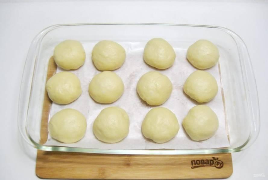 Разделите тесто на шарики весом приблизительно 80-85 граммов и выложите в форму для запекания.