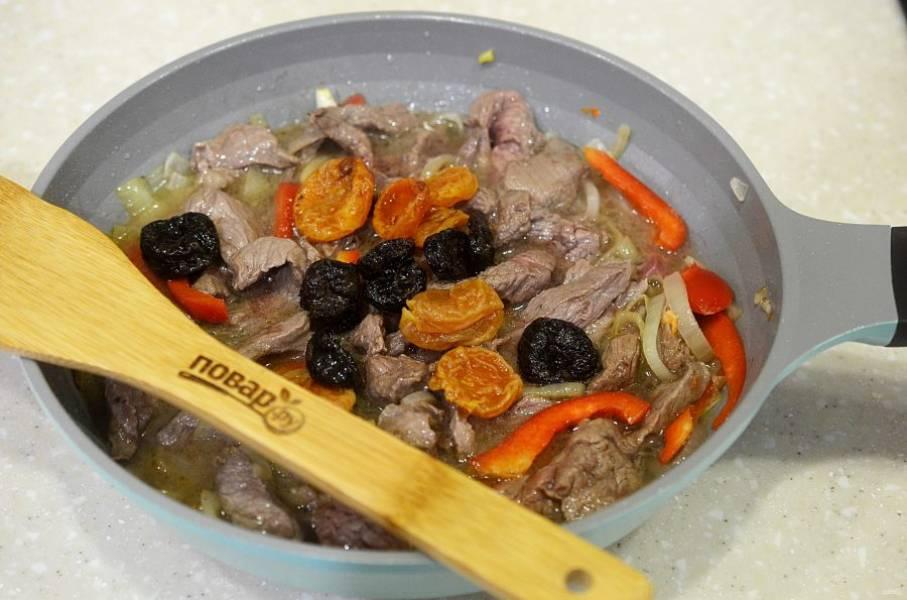 7. С сухофруктов слейте воду и добавьте к мясу. Тушите на небольшом огне около часа.