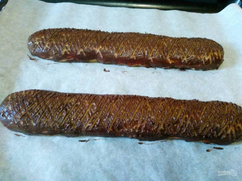 С помощью зубцов вилки сделайте на поверхности колбасок узор из полосок разного направления. Поместите будущее печенье в духовку, разогретую до 180 градусов.