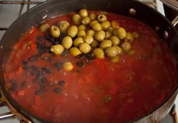 4. Овощи тушатся около 5 минут на медленном огне, после чего к ним следует добавить оливки и горошек. Некоторые для этого блюда используют еще и изюм. По желанию и вкусу - добавьте и его 1 щепотку.  Теперь протушите еще несколько минут овощи, после чего отправьте в сковороду обжаренное мясо. Я обычно использую две сковороды - одна для мяса, другая для овощей и делаю блюдо одновременно.