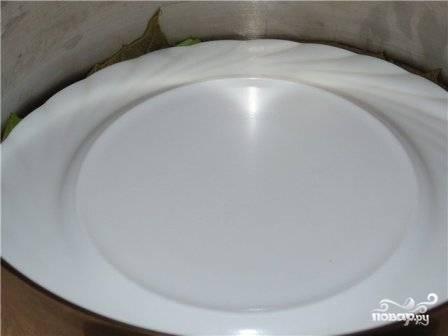 Сверх застилаем листьями и кладем тарелку, чтобы наши изделия не всплывали во время готовки. Заливаем примерно 2 стаканами слегка подсоленной воды, добавляем сок половинки лимона и 2-3 ложки масла. Варим на маленьком огне примерно 1 час после закипания.