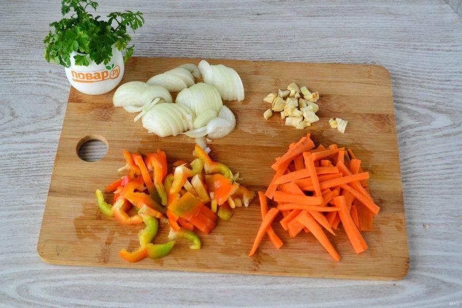 Тоненькими брусочками нарежьте морковь, соломкой нарежьте сладкий перец, лук нарежьте полукольцами, мелко нарежьте чеснок.