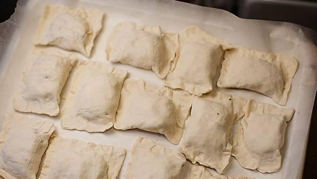 На край прямоугольников кладем по 1 ст. л. начинки. Сформируйте пирожки, края защипните. Смажьте пирожки смесью желтка с молоком. Застелите противень пекарской бумагой, выложите на него пирожки и выпекайте их в духовке 20 минут, температура 180 градусов.