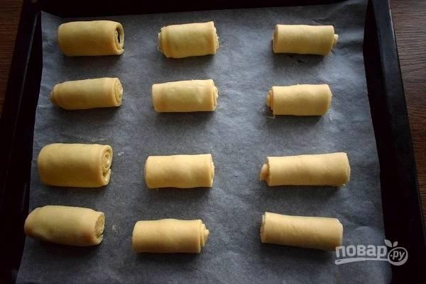 Противень застелите пергаментом для выпечки. Прямоугольники сверните в рулетики и выложите на пергамент (краем вниз). Накройте пищевой пленкой и оставьте в теплом месте на 20 минут.