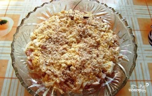 Натрите орехи на терке или измельчите их при помощи блендера. Аккуратно выложите третьим слоем.