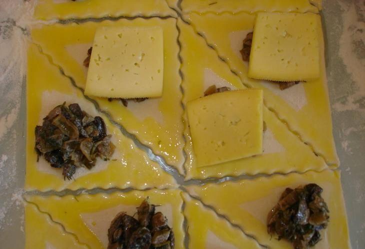 Треугольники теса смазываем желтком. В центр каждого треугольника, кладем начинку. Сверху кладем по кусочку сыра.