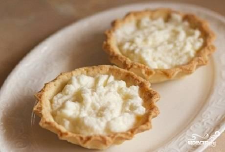 Взбейте сливки вместе с сахаром. Также слегка взбейте сливочный сыр. Соедините сыр и сливки. Получившуюся массу выложите в тарталетки.