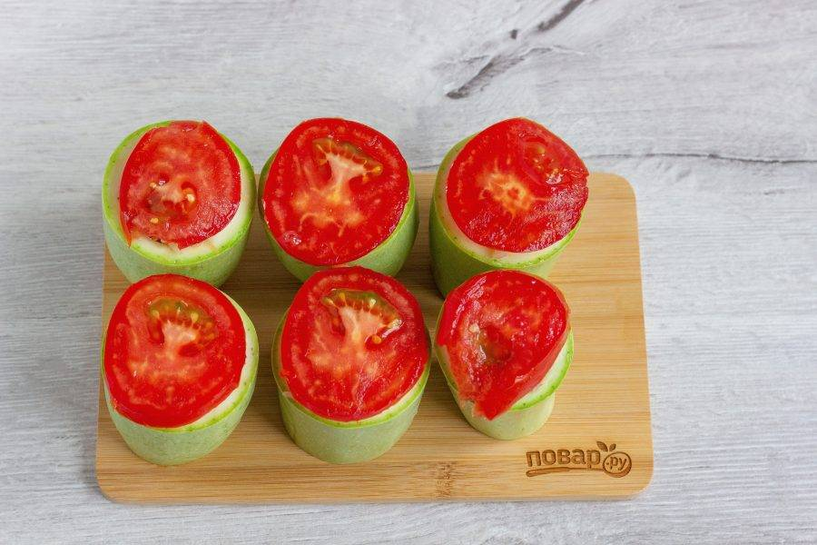 Наверх каждого кабачка положите кружок помидора.