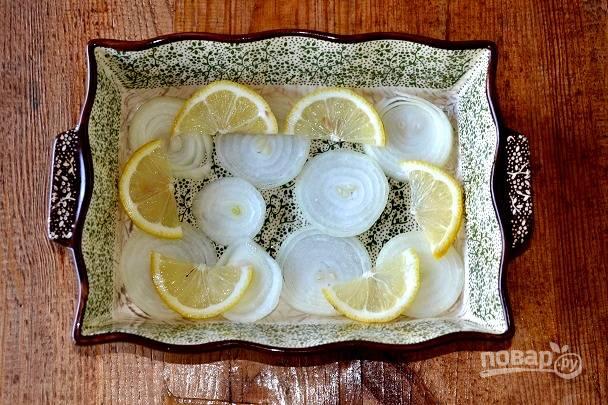 На дно жаропрочной формы выложите нарезанный тонкими кольцами лук и лимон.