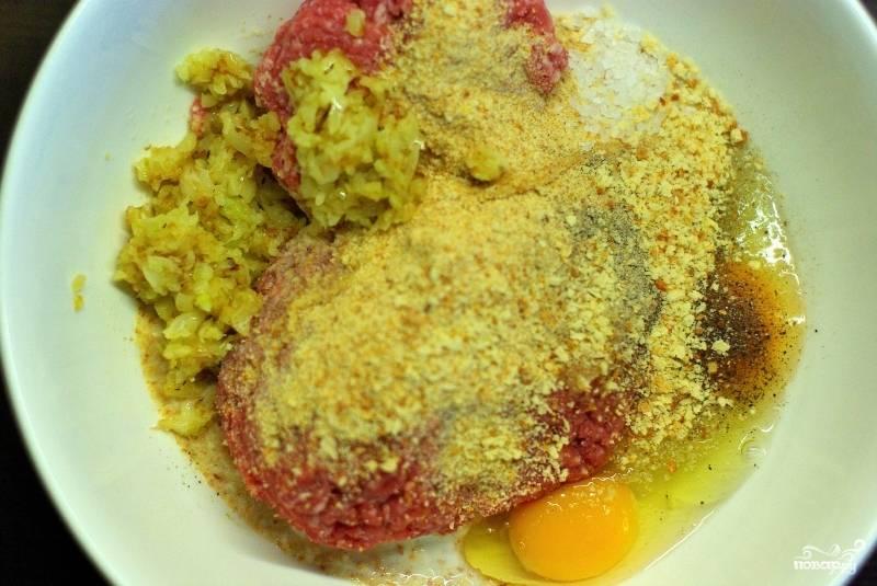 Затем в удобной посуде смешиваем: обжаренный лук, говяжий и свиной фарш, яйца, соль, перец, панировочные сухари, молоко.