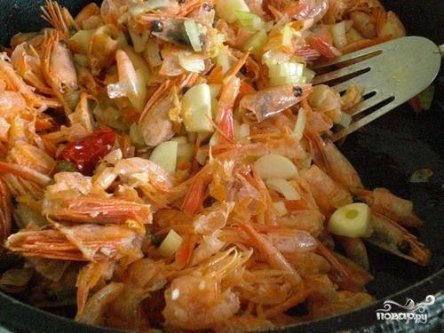Кладем в сковороду панцири креветок (мясо пока оставляем в сторонке), лук, чеснок, имбирь и перец. Тушим около 10 минут на слабом огне.
