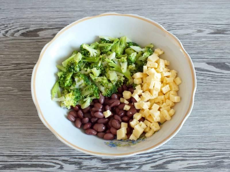 Размороженную брокколи разберите на соцветия, переложите в салатник. Сыр нарежьте кубиком, переложите к брокколи. Также добавьте отварную фасоль.