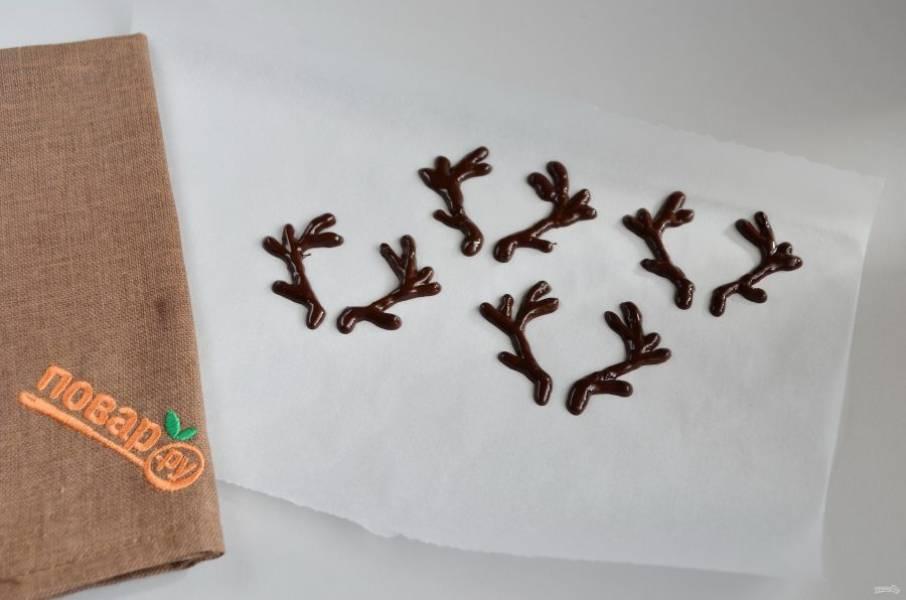 5. Нарисуйте шоколадом рога. Не стоит рисовать очень тонкие рога, они могут поломаться в процессе. И слишком большие тоже не делайте, тяжелые массивные рога будут выпадать из мягкого банана. Отправьте рожки в морозилку или в холодильник для застывания.