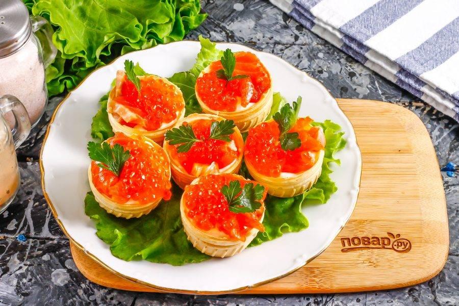 Украсьте тарталетки свежей зеленью укропа или петрушки, посолите и поперчите по вкусу. Выложите их на листья салата или другую зелень.