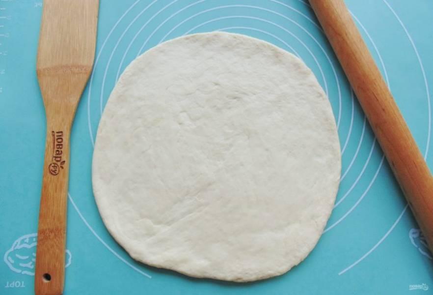 Тесто достаньте из миски, обомните и разделите на две части. Одна часть должна быть больше, другая чуть меньше. Раскатайте большую часть в пласт.