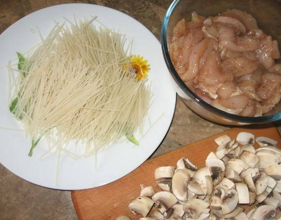 Курицу режем на кусочки, заправляем соевым соусом, хересом и специями. Отставьте на 15 минут. Тем временем, отварите лапшу и откиньте на дуршлаг. Грибы порежьте ломтиками.