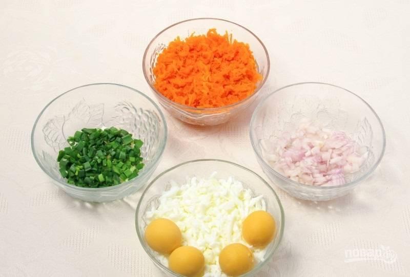 2.Отвариваю яйца и отделяю желтки от белков, последние измельчаю на крупной терке. Морковь отвариваю и остужаю, затем натираю на крупной терке. Репчатый и зеленый лук мою, затем измельчаю.