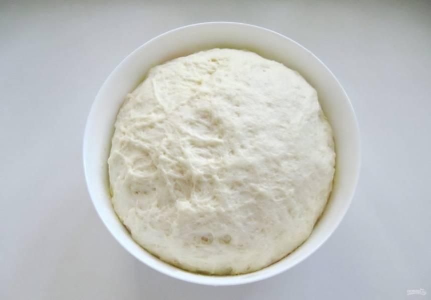 Накройте тесто пищевой пленкой и поставьте в теплое место. Через 50-60 минут оно значительно увеличится в объеме.