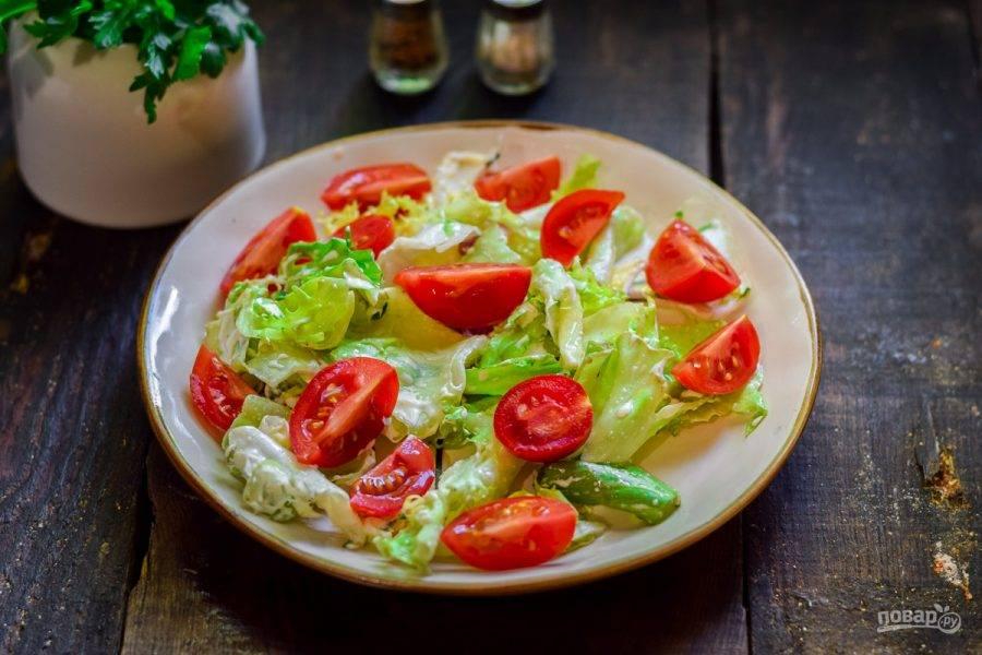Томаты черри сполосните и нарежьте дольками. Добавьте помидоры в салат.