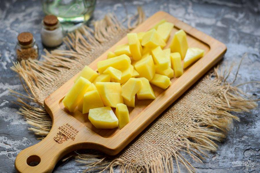 Очистите клубни картофеля, сполосните, просушите. Нарежьте картофель небольшими по размеру кусочками.