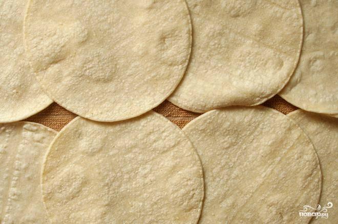 3. Пока чечевица готовится, разогреть духовку до 135 градусов. Выложить смоченное водой кухонное полотенце на противень. Выложить лепешки на полотенце в один слой (незначительное перекрытие допускается), сверху выложить второе влажное полотенце. Нагреть в духовке в течение 10 минут, пока лепешки не станут теплыми и мягкими.