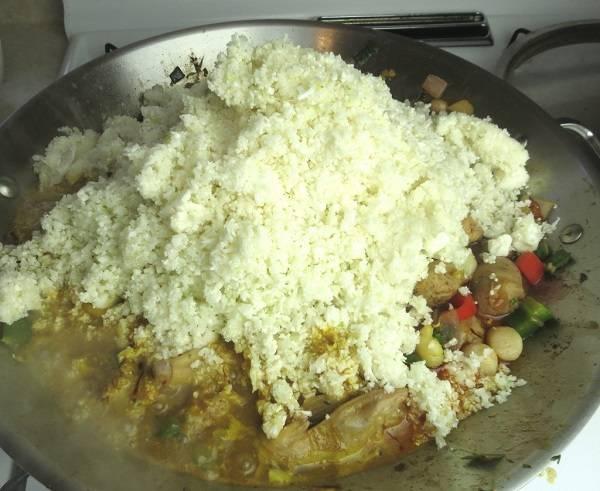 6. Всыпать на сковороду рис. Паэлья с курицей и овощами в домашних условиях может готовиться на воде или на заранее приготовленном овощном бульоне, который нужно влить сразу после добавления риса.