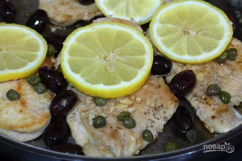 4.Выложите в соус кусочки мяса, выложите вокруг оливки и каперсы. Нарежьте лимон кусочками и выложите на курицу.