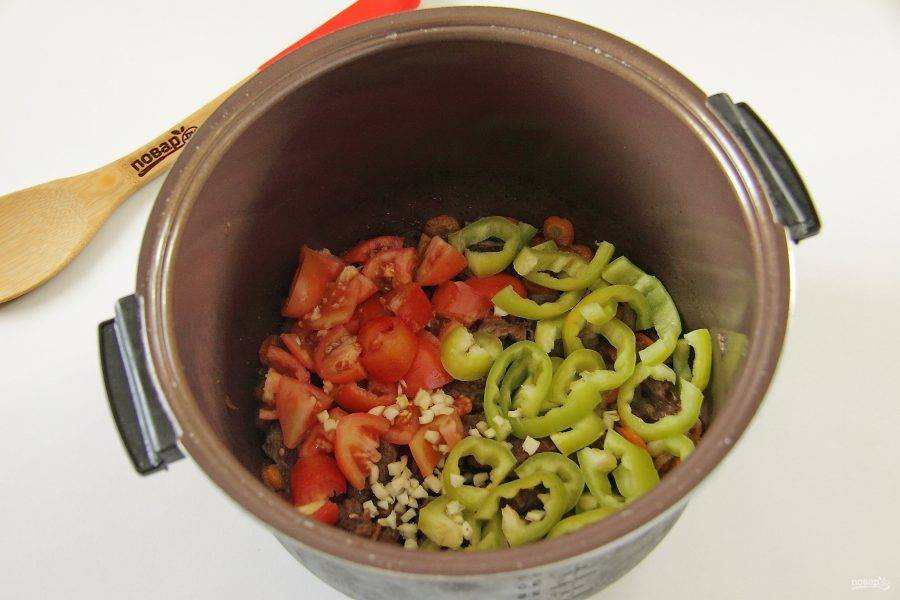 """5. Установите режим """"тушение"""" или используйте функцию """"мультиповар"""" и тушите мясо 1,5 часа. За несколько минут до готовности, крышку можно открыть, чтобы испарилась большая часть жидкости. В конце добавьте нарезанный соломкой перец, нарезанные кубиками помидоры и измельченный ножом чеснок."""