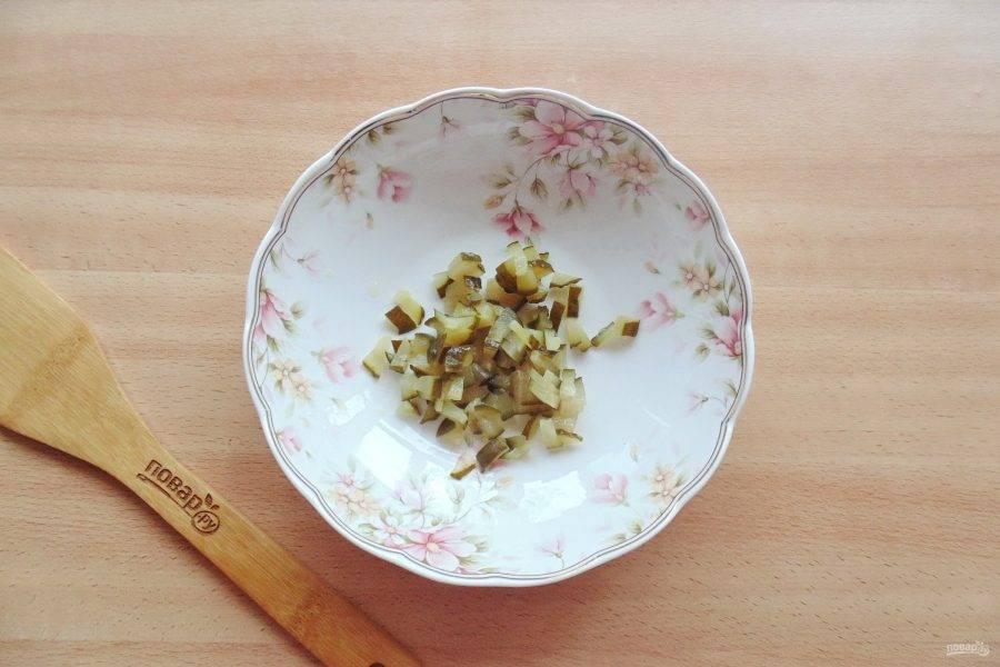 Соленый или маринованный огурец мелко нарежьте и выложите в салатник.