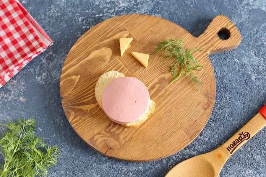 Накройте сыр кружочком колбасы, который будет имитировать мордочку.