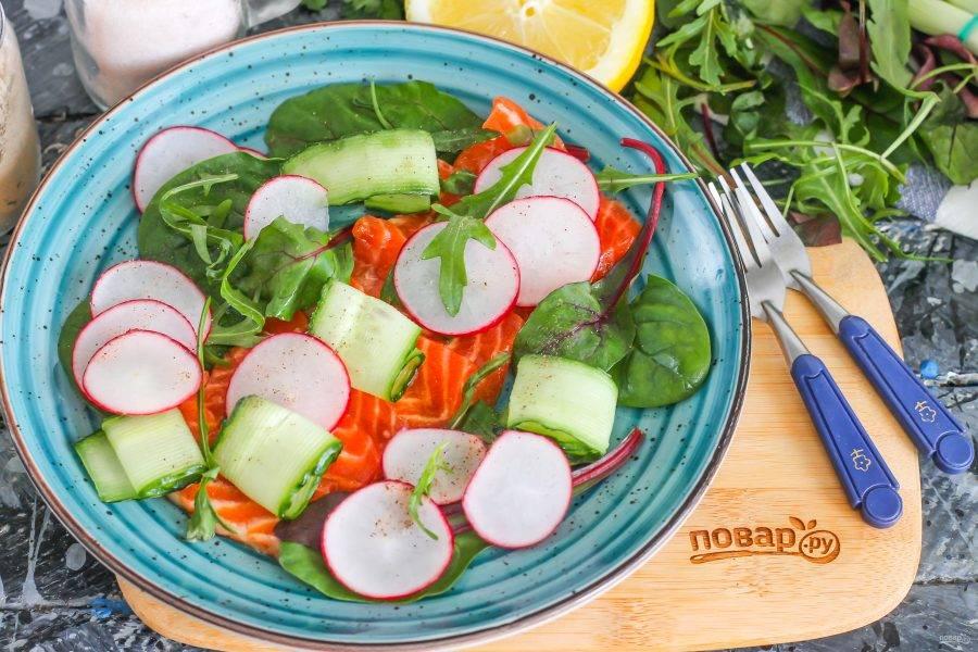 Тонко нарежьте промытые овощи, сначала срезав с обеих сторон хвостики. Выложите овощные нарезки на мякоть рыбы и сбрызните оставшимся соусом. Слегка поперчите.