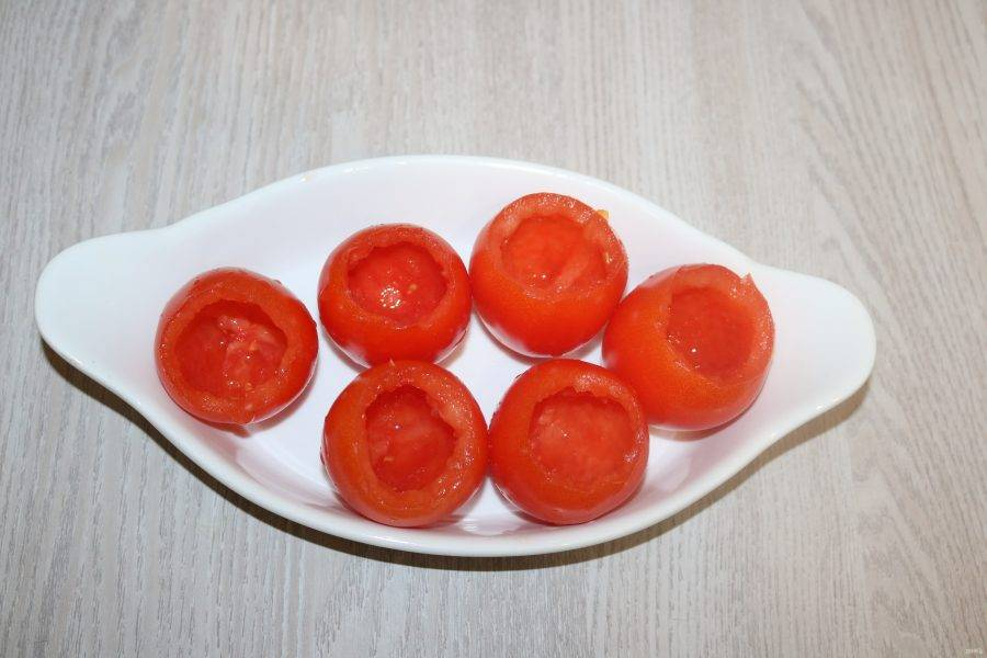 Помидоры помойте, аккуратно удалите сердцевину. Выложите подготовленные помидоры в форму для запекания.