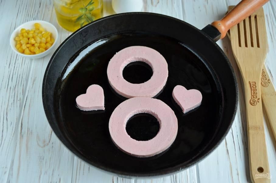 Разогрейте сковороду, смажьте её рафинированным маслом. Обжарьте колбасу и сердечки немного.