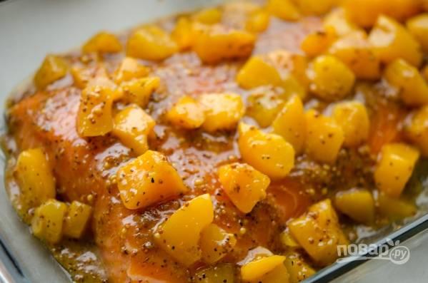 Рыбу поместите на противень, выложите сверху персики и накройте фольгой.