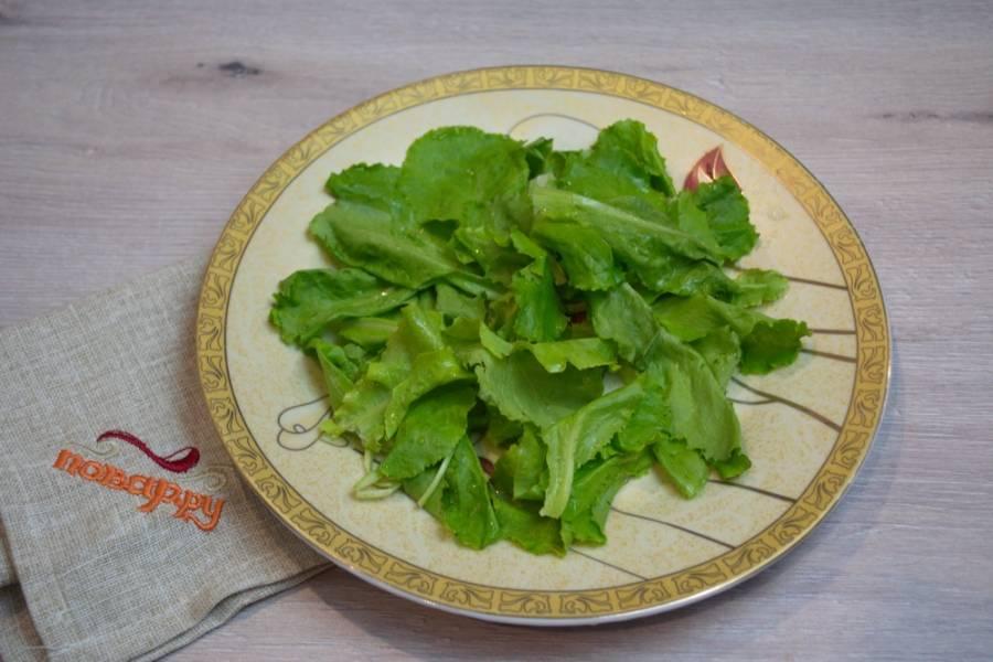 Поставьте яйца отвариваться вкрутую. На презентационное блюдо выложите вымытые и хорошо просушенные листики салата.