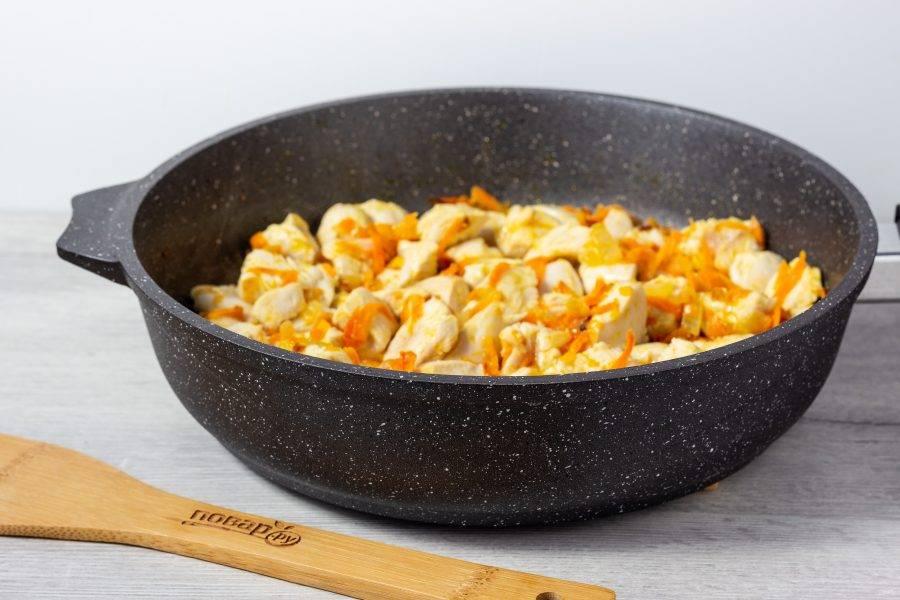 Пока овощи жарятся, нарезаем кубиками филе куриной грудки. Отправляем на сковороду, помешиваем и солим по вкусу. Когда  каждый кусочек курицы станет светлым, можно добавлять рис.