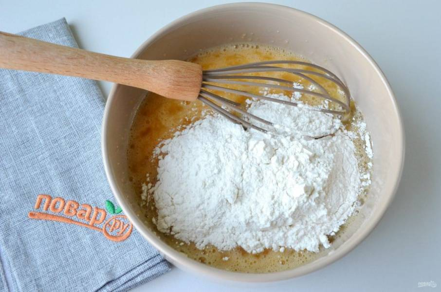 3. Всыпайте просеянную муку небольшими порциями, замешивайте тесто, венчиком разбивайте комочки.