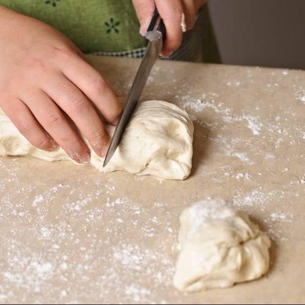 Когда тесто поднимется, разрежьте его на 10 одинаковых кусочков, на заранее присыпанной мукой поверхности.