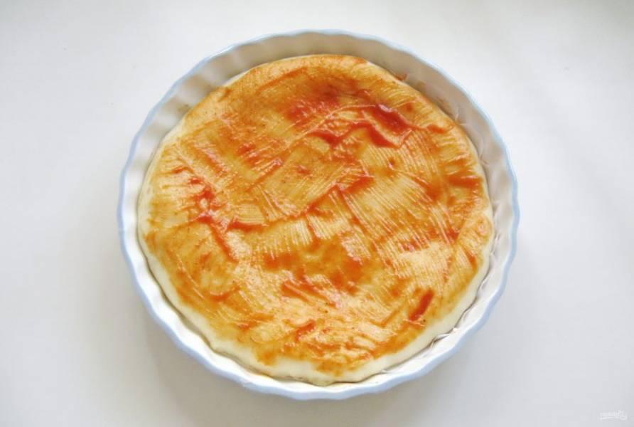 Достаньте тесто из духовки и смажьте кетчупом.