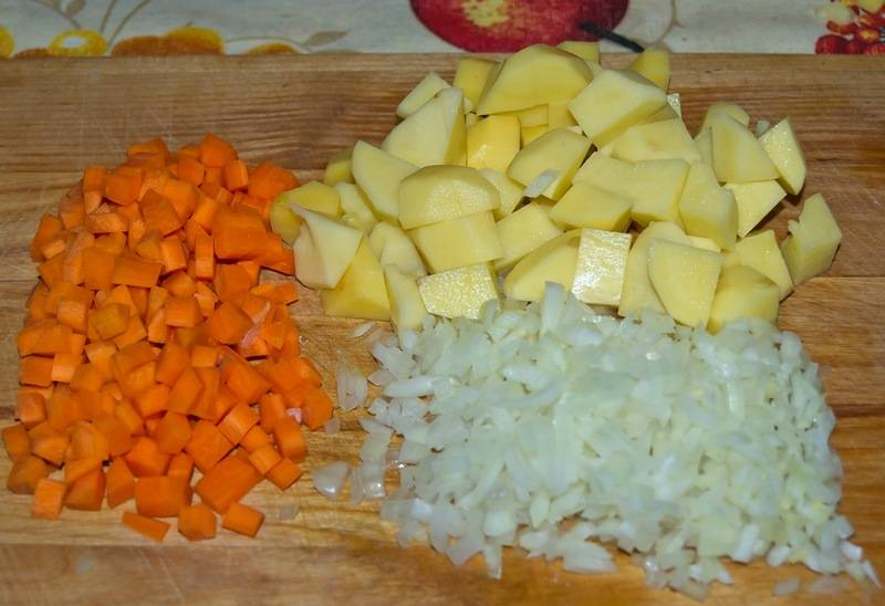 Пока варится мясо, очищаем овощи и нарезаем морковь на мелкие кубики, картофель режем чуть побольше, репчатый лук измельчаем.