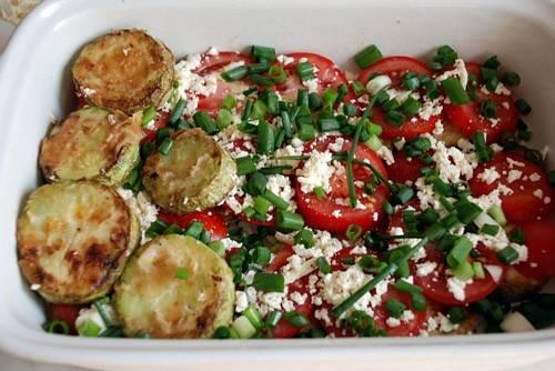 Потом опять выкладываем колечки кабачка и помидоры, посыпаем все брынзой и луком.