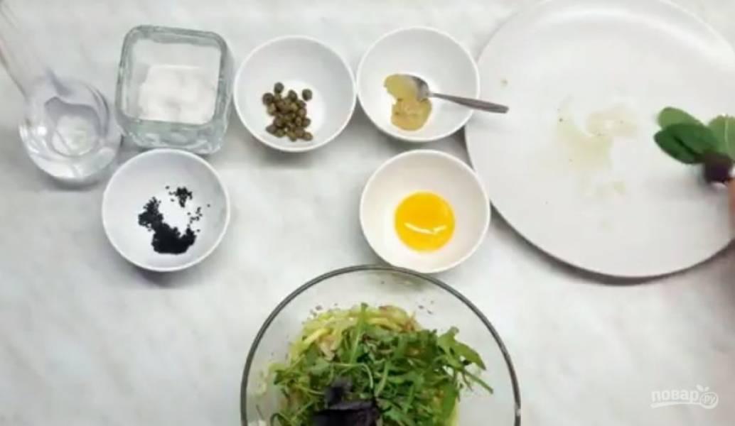 2.  Яйцо сварите и разрежьте на четыре части. Добавьте консервированный тунец, перемешайте и добавьте зелень по вкусу: рукколу, базилик и мяту. Приготовьте заправку: желток смешайте с горчицей, солью и уксусом.