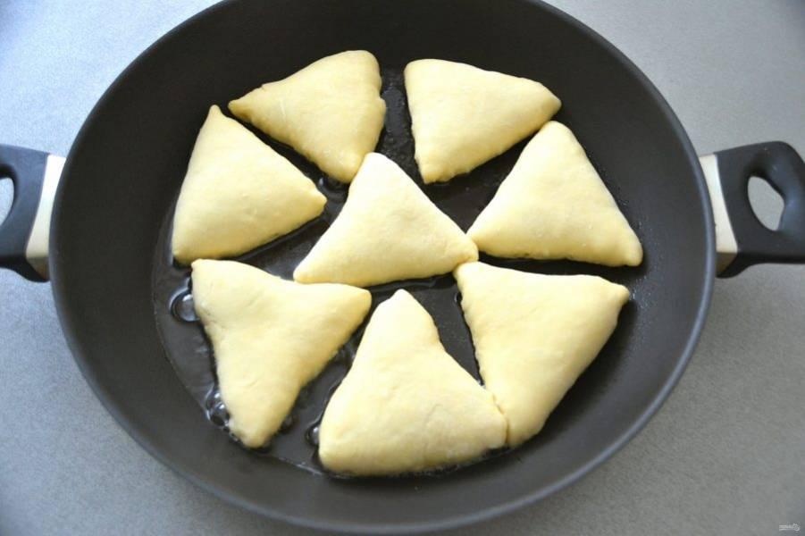 Влейте растительное масло на сковороду, как следует разогрейте, выложите беляши отверстием вниз.