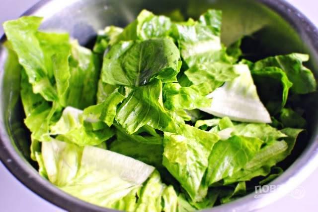7. Салат вымойте, обсушите и нарвите руками. Выложите в салатник.